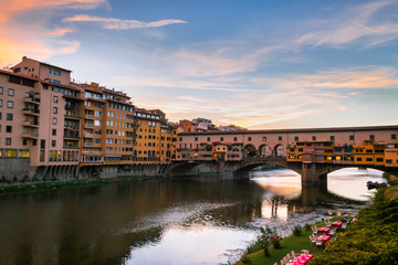 View with a unique perspective of the Ponte Vecchio with the river Arno and colorful buildings in the city of Florence at sunset, Florence, Tuscany, Italy, Europe