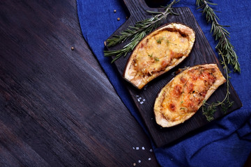 Stuffed eggplant halves roasted with cheese on a black cutting board