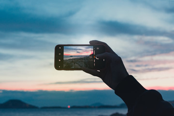 hand holding smart phone with landscape background with copy space