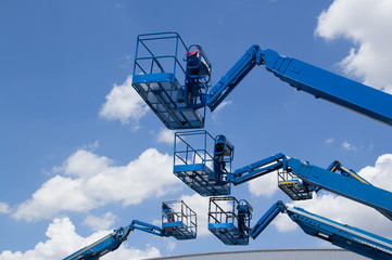 blue cherry picker over the metal factory roof against blue sky. Lift buckets machine.