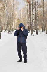Young man taking pictures standing on the road in the winter Park.