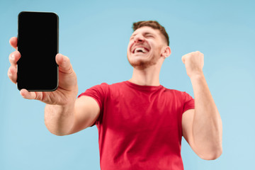 Young handsome man showing smartphone screen over blue background with a surprise face. Human emotions, facial expression concept. Trendy colors