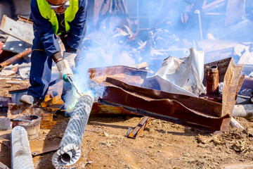 Worker is cutting scrap metal with acetylene torch
