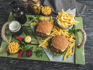 Fototapete - Burger pulled beef barbeque , sandwich, french fries, sauce, dark beer, corn, on a wooden tray