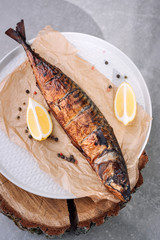 Smoked fish with lemon slices and pepper on backing paper on wooden smoking background, top view.