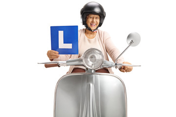 Senior woman with on vintage scooter holding a learning plate