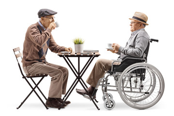 Senior man sitting and drinking coffee with a disabled man in a wheelchair
