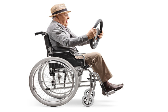 Elderly man sitting in a wheelchair and holding a steering wheel from a car