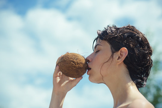 coconut oil production. Clean eating diet, vegetarian and vegan. Woman is moisturizing her skin with a coconut cream. drinking beach cocktail. coco milk. woman drinking coconut juice. summer vacation