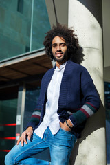 Portrait of handsome young Afro American man in casual clothes, looking camera and smiling while leaning on a column, standing outdoors