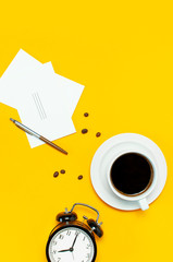 Flat lay cup black coffee, coffee beans, black alarm clock, pens, white cards on yellow background top view copy space. Creative Concept time to work, female desktop, coffee background