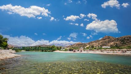 Agia Galini Beach in Crete island, Greece. Tourists relax and bath in crystal clear water of Agia Galini Beach.