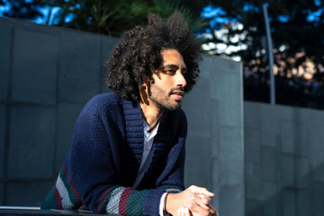 Portrait of handsome Afro American man in casual clothes, looking away and laughing while leaning on a fence, standing outdoors