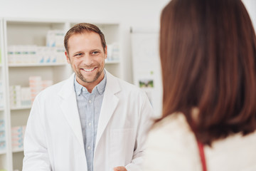 Male pharmacist smiling as he attends to a woman