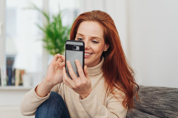Smiling woman typing in a text message