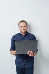 Man with laptop standing against white wall