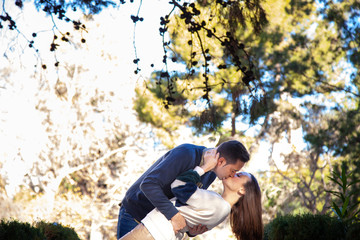 A young couple in love kiss each other like in a movie scene in a public park.