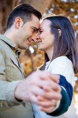 Young couple flirts in a public park with hands intertwined in the foreground