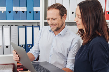 Man and woman working with laptop together