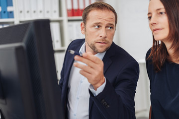 Man showing something on display to his colleague