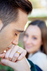 Man kisses the hand of his girlfriend who appears out of focus in the background