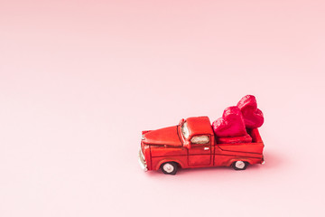 A small toy car carries candy in the shape of hearts on a pink background. Valentine's day concept. greeting card.Love.selective focus.