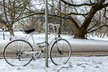 White bicycle with lock locked at street sign. City winter landscape.