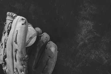 Black and white baseball image with old vintage ball in used grunge leather mitt.
