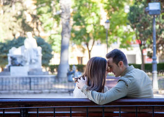 Rear view of a young couple in love flirting on the bench of a public park in daylight