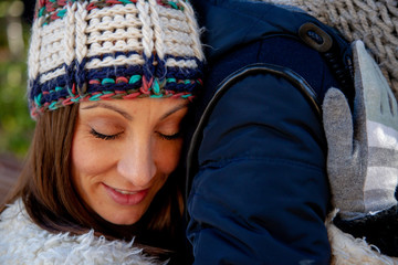 Young woman dressed in winter gloves and woolen hat hugs in love and with eyes closed to her boyfriend from behind