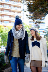 Young bride and groom walk hand in hand through a public park dressed in winter wool hats.