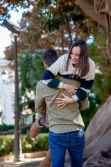 A boy takes his girlfriend in his arms in a public park