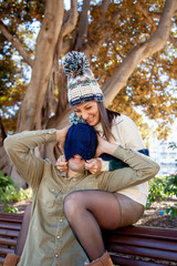A couple plays with a woolen hat in a public park