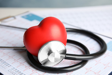 Stethoscope, red heart and cardiogram on table. Cardiology concept Wall mural