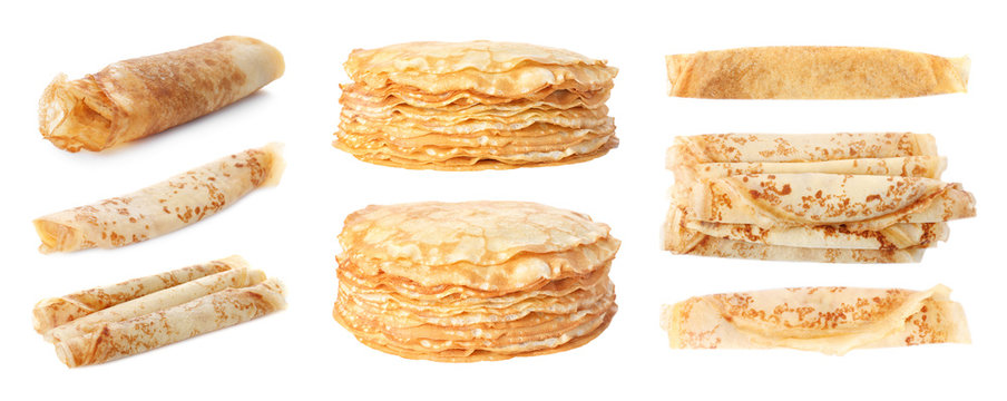 Set of rolled and stacked tasty thin pancakes on white background