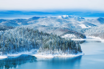 Croatian nature landscape, beautiful winter panorama of Lokvarsko lake and woods under snow in Gorski kotar and Risnjak mountain in background
