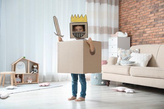 Cute little boy playing cardboard armor in living room