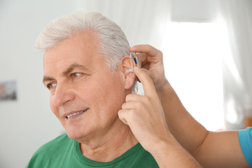 Young man putting hearing aid in father's ear indoors