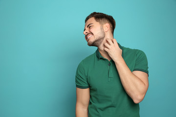 Young man scratching neck on color background, space for text. Annoying itch