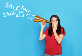 Emotional young woman with megaphone and words SALE on color background