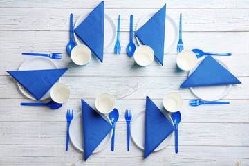 Table setting with plastic dishware on wooden background, flat lay
