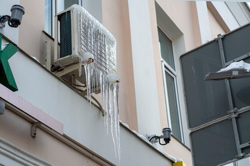 Street block conditioner frozen and covered with icicles and snow in winter