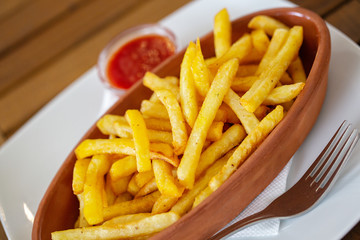 Clay oval plate of french fries on a wooden table