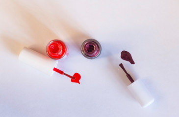 Bottles of colorful nail polish with their brushes displayed against a white background.