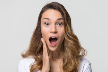 Amazed funny young woman girl with surprised wow face open mouth stunned looking at camera feeling excited astonished shocked isolated on white light background studio wall, head shot portrait