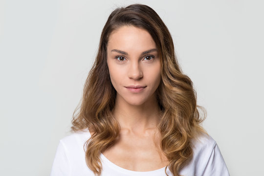 Head shot of young female with beautiful face, millennial woman looking at camera on white grey background, smiling pretty girl attractive model isolated against blank studio wall, portrait image