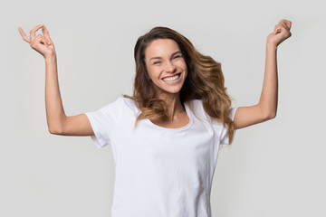 Happy cheerful young woman jumping feeling joy isolated on white studio wall blank background, excited ecstatic girl laughing rejoicing dancing enjoying freedom looking at camera, portrait