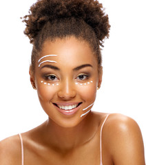 Face lifting. Smiling african american girl with rejuvenating cream on her face on white background. Skin care and beauty