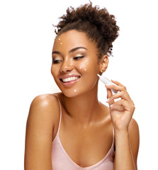 Happy girl applying treatment cream. Photo of smiling african american girl isolated on white background. Skin care concept