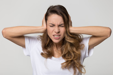 Fototapeta Annoyed stressed woman cover ears feel hurt ear ache pain otitis suffer from loud noise sound headache, irritated stubborn girl deaf hear not listen to noisy music isolated on white studio background